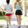 Rear View Of Two Female Runners On SuburbStreet — Stock Photo #27554295