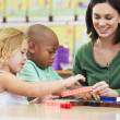 Elementary Pupils Counting With Teacher In Classroom — Stock Photo #27554377