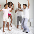 Family Jumping On Bed Together — Stock Photo #27554389