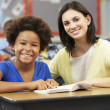 Teacher Reading With Female Pupil In Class — Stock Photo #27554427