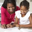 Mother Helping Daughter With Homework In Kitchen — Stock Photo