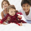 Children Sitting On Bed In Pajamas Together — Stock Photo #27554839