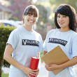 Stock Photo: Portrait Of Two Female Charity Volunteers On Street