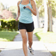 Female Runner Exercising On Suburban Street — Stock Photo
