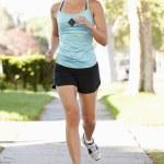 Female Runner Exercising On Suburban Street — Stock Photo