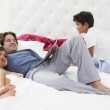 Father And Children Relaxing In Bed Together — Stock Photo #27555063