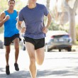 Male Runners Exercising On Suburban Street — Stock Photo