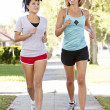 Two Female Runners Exercising On SuburbStreet — Stock Photo #27555449