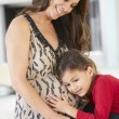 Daughter Listening To Pregnant Mother's Stomach — Stock Photo
