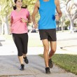 Stock Photo: Couple Running On SuburbStreet