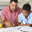 Stock Photo: Father Helping Son With Homework In Kitchen