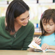 Elementary Pupil Reading With Teacher In Classroom — Stock Photo #27555793