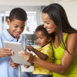 Mother And Children Using Digital Tablet In Kitchen Together — Stock Photo #27555891