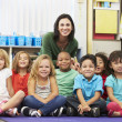 Group of Elementary Pupils In Classroom With Teacher — Stock Photo #27555899