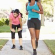 Two Female Runners Exercising On SuburbStreet — Stock Photo #27556047