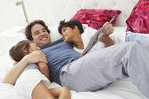 Far och barn slappar i sängen tillsammans — ストック写真