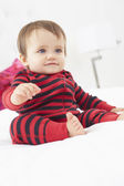 Toddler Sitting On Bed Wearing Pajamas — Stock Photo