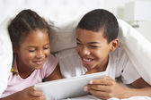 Two Children Using Digital Tablet Under Duvet — Stock Photo