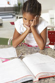 Fed Up Girl Doing Homework In Kitchen — Stok fotoğraf