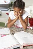 Trött tjej gör läxor i köket — Stockfoto