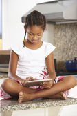 Girl Sitting On Kitchen Counter With Digital Tablet — Stock Photo