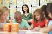 Grupo de crianças em idade primária na aula de arte com professor — Foto Stock