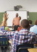 Male Pupil Raising Hand In Class — Stock Photo
