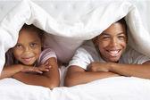 Two Children Hiding Under Duvet In Bed — Stock Photo