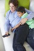 Overhead View Of Father And Son Relaxing On Sofa Watching TV — Stock Photo