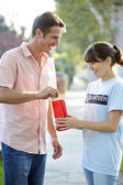 Charity Worker Collecting From Man In Street — Stock Photo