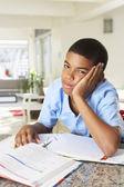 Trött pojke gör läxor i köket — Stockfoto