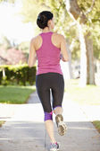 Rear View Of Female Runner Exercising On Suburban Street — Stock Photo