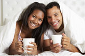 Couple Relaxing In Bed With Hot Drink — Stock Photo