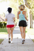 Rear View Of Two Female Runners On Suburban Street — Stock Photo