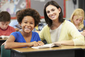 Teacher Reading With Female Pupil In Class — Foto Stock