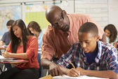 Teacher Helping Male Pupil Studying At Desk In Classroom — Stock Photo