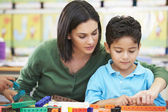 Elementary Pupil Counting With Teacher In Classroom — Stock Photo