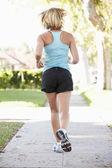 Rear View Of Female Runner Exercising On Suburban Street — Stock Photo