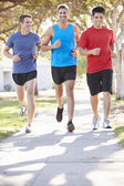 Group Of Male Runners Exercising On Suburban Street — Stock Photo