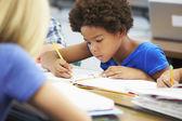 élèves étudient à un bureau dans la salle de classe — Photo