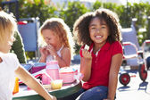 Elementary Pupils Sitting At Table Eating Lunch — Stock Photo