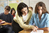 Teacher Helping Female Pupil Studying At Desk In Classroom — Stock Photo