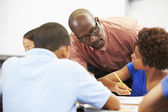 Teacher Helping Pupils Studying At Desks In Classroom — Stock Photo