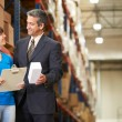 Stock Photo: BusinessmAnd Female Worker In Distribution Warehouse