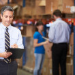 Manager In Warehouse Writing On Clipboard — Stock Photo