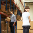 Businesswoman Pulling Pallet In Warehouse — Stock Photo