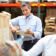 Stock Photo: Manager In Warehouse With Worker Scanning Box In Foreground