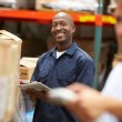 Manager In Warehouse With Worker Scanning Box In Foreground — Stock Photo #36835699