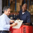 Fork Lift Truck Operator Talking To Manager In Warehouse — Stock Photo