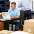 Worker In Warehouse Wearing Headset And Using Laptop — Stock Photo